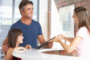 Family filling out insurance information at reception desk